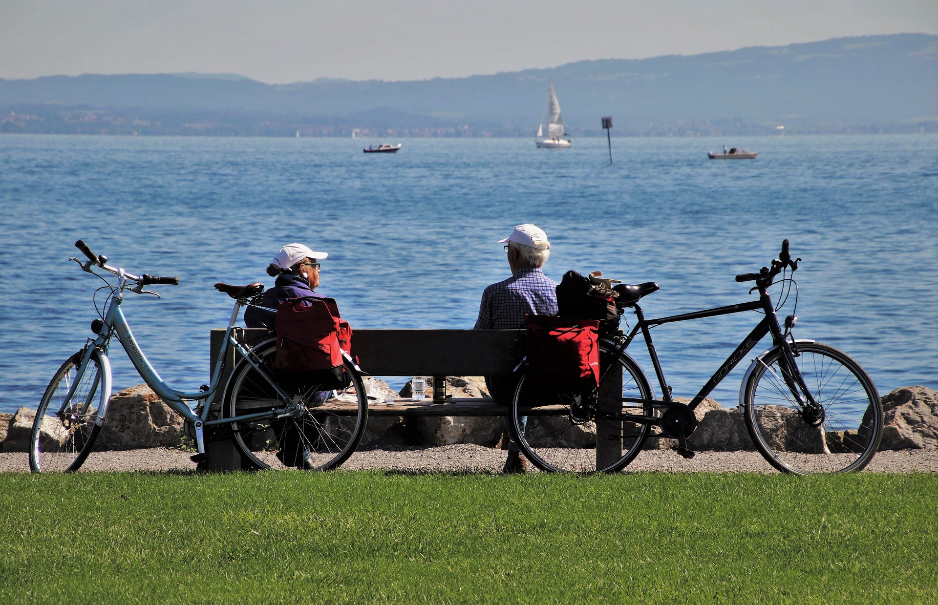 Older couple sitting on a bench after a bike ride on the water
