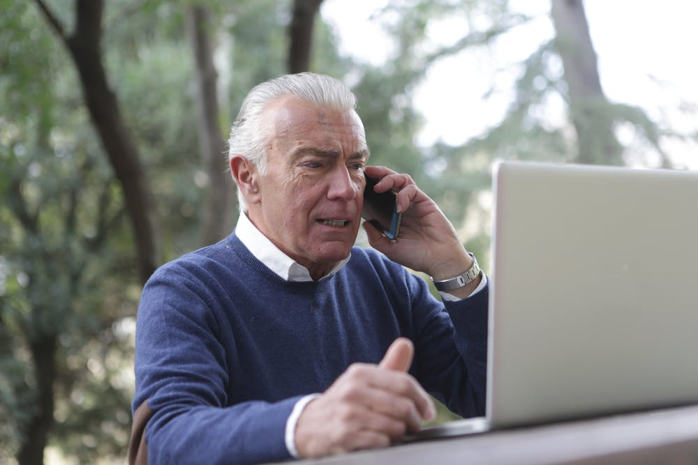Frustrated elderly man on his phone and computer