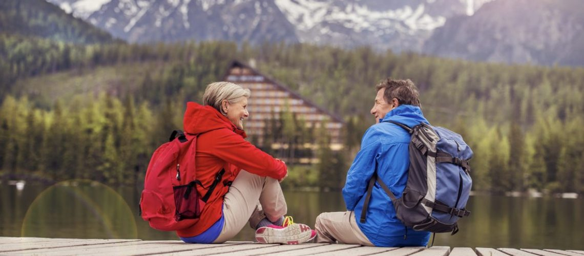 Elderly couple sitting in the mountains talking